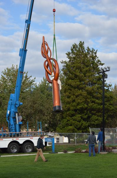 SPOTLIGHT PHOTO: COURTNEY VAUGHN - A crane carries a 20-foot sculpture from a truck bed to the newly installed Columbia County Rotary Children's Fountain at Heritage Park in Scappoose Monday, Oct. 2. The sculpture completes the fountain, which has been a nearly decade-long project.