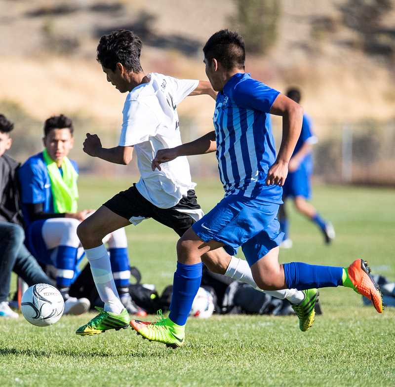 LON AUSTIN/CENTRAL OREGONIAN - Vicente Ramirez, in white, pushes the ball up the sideline past Madras defender Yehir Aguirre. Although Ramirez was able to control the ball, the White Buffalos controlled the match, taking a 9-1 victory.