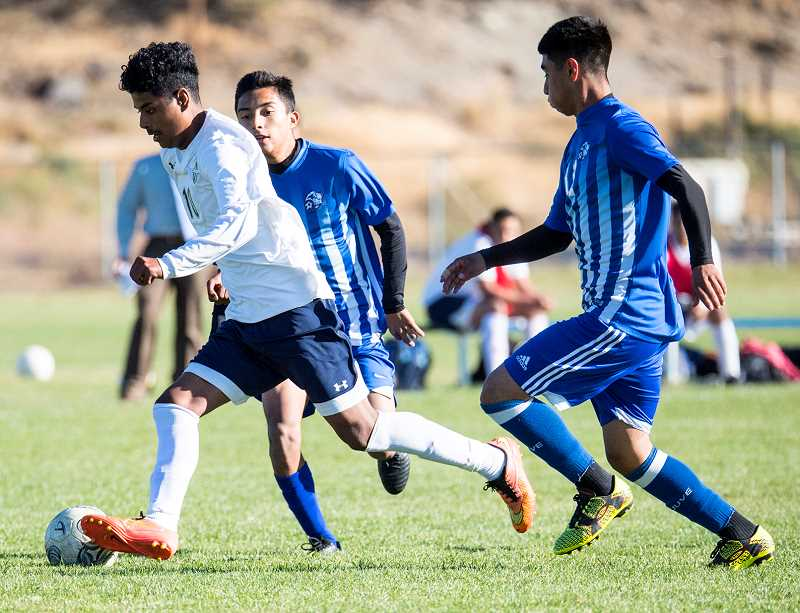 LON AUSTIN/CENTRAL OREGONIAN - Elias Villagomez pushes the ball past a pair of Madras defenders during the first half of the Cowboys' loss to the White Buffalos on Tuesday. Villagomez had an assist on the lone Crook County goal in the match.