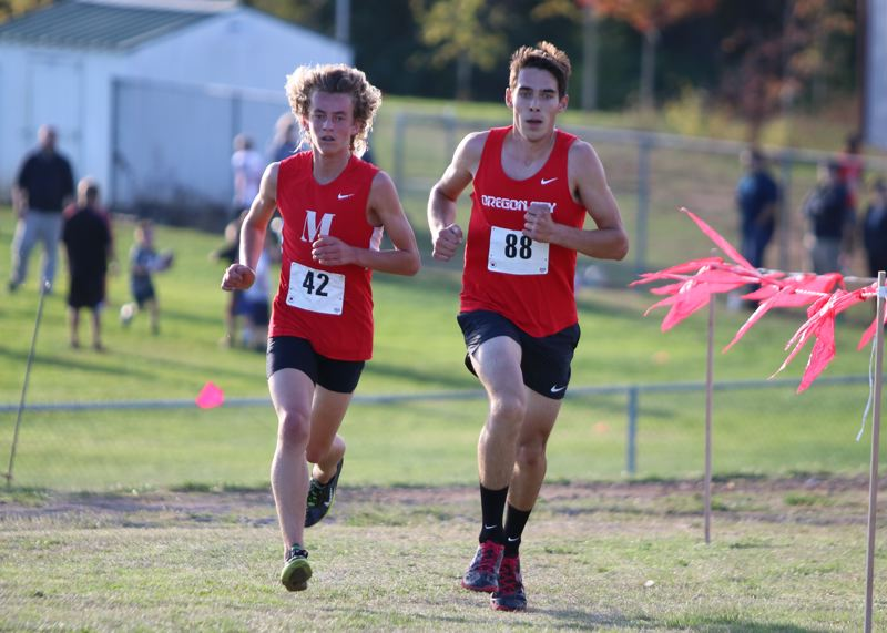REVIEW/NEWS PHOTO: JIM BESEDA - Madison's Gus Harquail (42) surges past Oregon City's Calvin Bryant (88) near the end of the second mile at Wednesday's boys' cross country race at Oregon City High School.