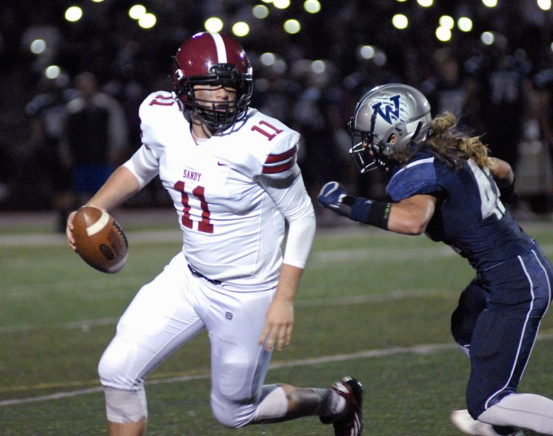 SANDY POST: MATT RAWLINGS - Sandy quarterback Tyler KIng tries to escape from a Wilsonville defender.