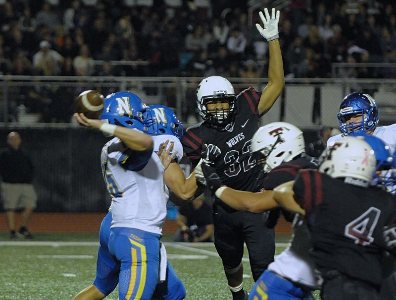SETH GORDON - Tualatin linebacker Dominique Loggins rises up to block the pass of Newberg quarterback Garrett Myers during the Timberwolves' 43-7 home victory Friday night.