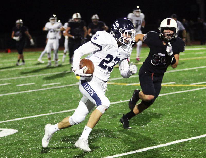 DAN BROOD - Lake Oswego sophomore Joe Hutson is on his way to scoring on a 60-yard pass play in Friday's game at Sherwood.