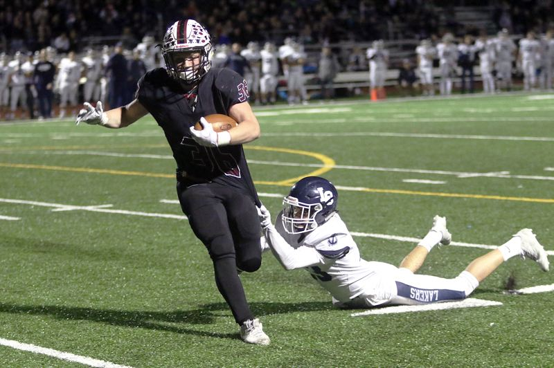 TIMES PHOTO: DAN BROOD - On the final play of the half, Lake Oswego sophomore Joe Hutson, and his Laker teammates dragged Sherwood senior running back Rustin Williams down for a four-yard loss as he tried to cut into LO's 12-point lead.