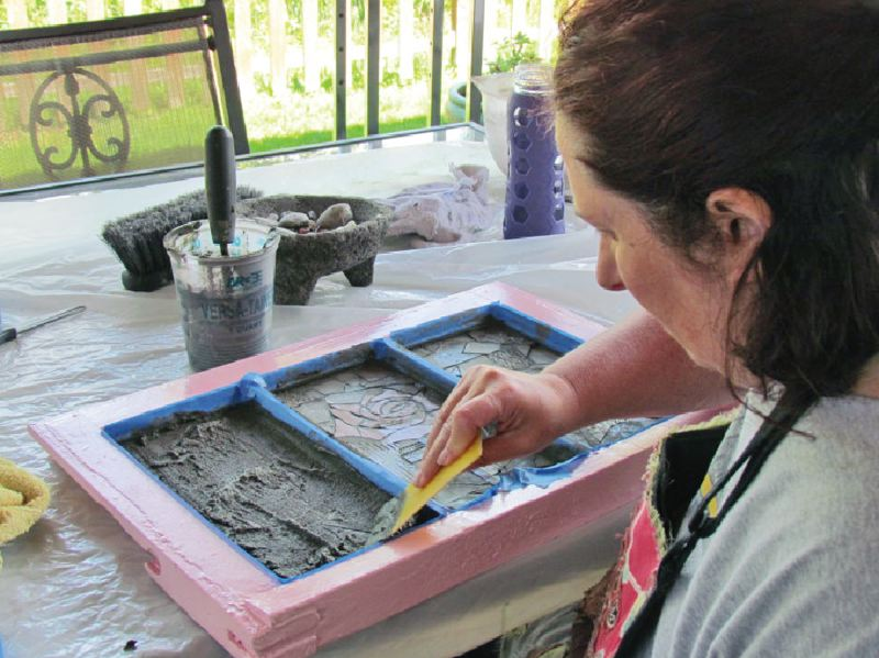 SUBMITTED PHOTO - Artist Darla Lynn is pictured above grouting one of her mosaics titled 'Gentle Roses.' She will be part of the Open Studios of Beavercreek event this weekend.