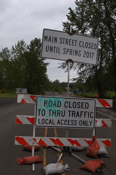 PHOTO BY: RAYMOND RENDLEMAN - Oregon City's original date for reopening Main Street near the entrance to the Clackamas River Trail was in spring of 2017, but city officials put up a new sign when the date passed.