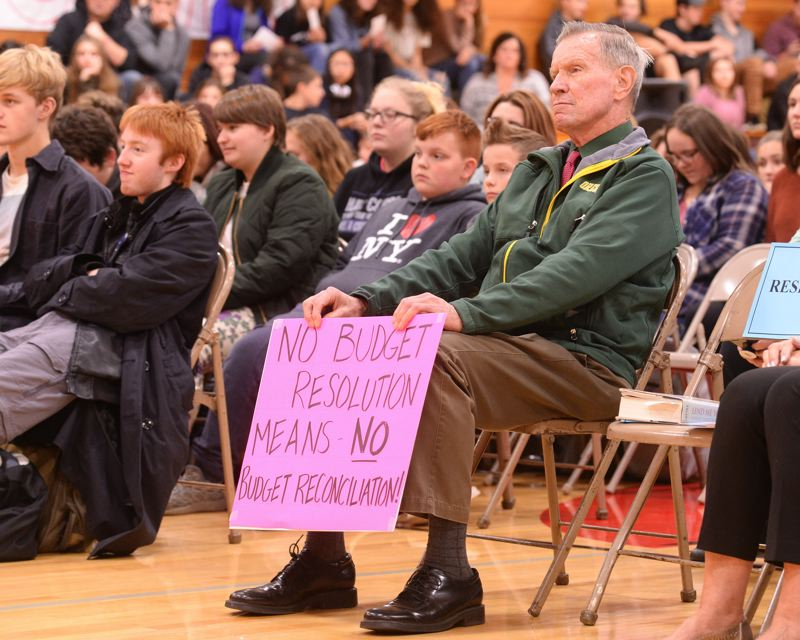 OUTLOOK PHOTO: JOSH KULLA - A man holds a sign during a town hall event with Sen. Ron Wyden, D-Oregon, in Corbett on Monday, Oct. 9.