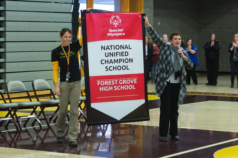 NEWS-TIMES PHOTO: CHRISTOPHER OERTELL - Forest Grove High School Special Education teacher Jill Hertell holds a banner with Jean Hansen, Vice President, School Partnerships and Youth Outreach for Special Olympics Oregon. The banner was presented to the school as one of only 38 schools in the country to receive the banner.