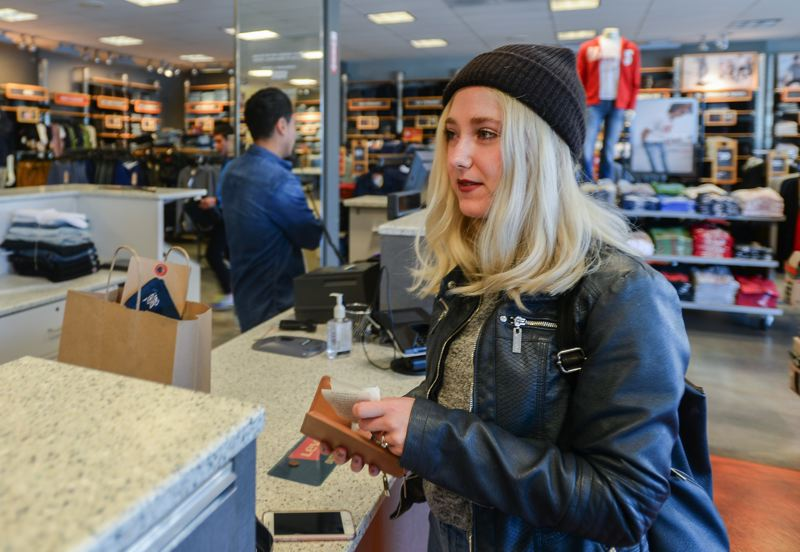 OUTLOOK PHOTO: JOSH KULLA - Madelin, a Portland resident, makes a purchase in the Levi's outlet store. She said she likes the ability to physically try on new clothes when visiting a store in person.