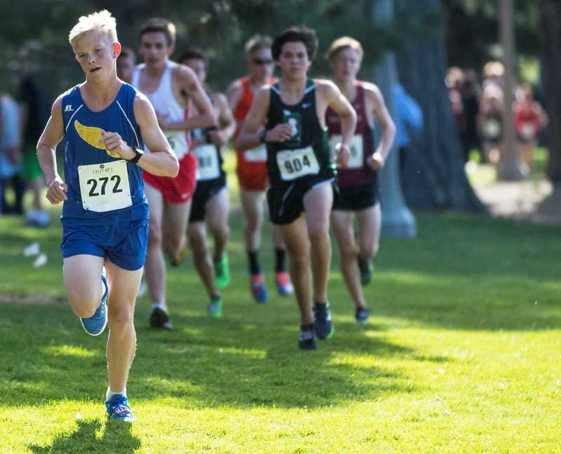 LON AUSTIN/CENTRAL OREGONIAN - Alex Carne leads a pack of runners midway through the boys varsity race at the Oxford Classics Invitational in Bend. Carne ran a personal best time of 17:41.38 to finish 31st overall and help lead the Cowboys to 13th place in the 26-team field.