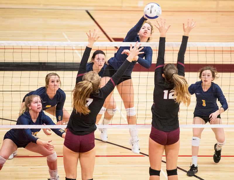 LON AUSTIN/CENTRAL OREGONIAN - Cassidy Dill hits a kill during bracket play against Sandy, while the rest of the Cowgirls cover her. Dill led Crook County in kills with 33 in the tournament.