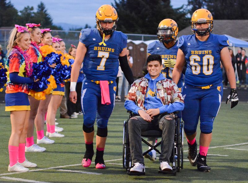 OUTLOOK PHOTO: DAVID BALL - Barlow High student Bobby Asa was all smiles while being escorted onto the field by teammates Austin Davis (7), Jobi Malary (background) and Triston Stauffer (60) pregame Friday night against Oregon City. Asa, a tight end on the junior varsity team last year, has spent the past several months recovering from injuries suffered in a car crash during the summer.