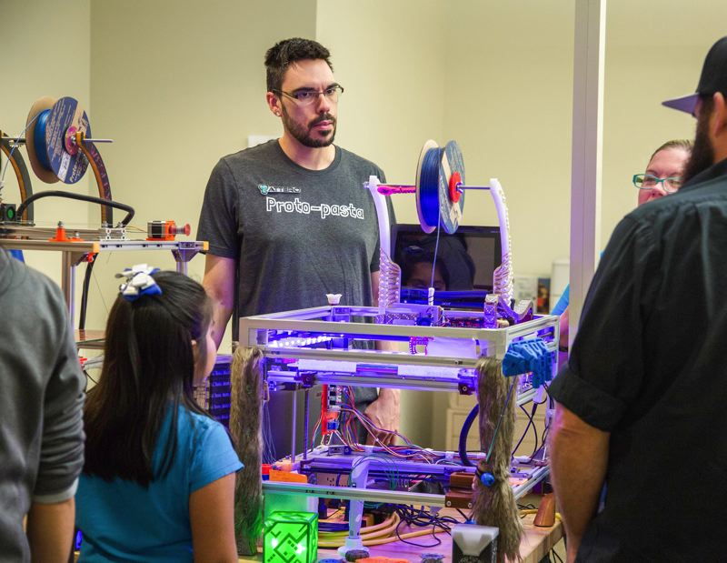"PHOTO: CAL STUDENT ADRIENNE ""ADRIE"" SLAWIK   - Ben Grove from the Gresham gift and toy company Maz and Attero demonstrates a 3D printer at the Makers Gone Pro event at the Center for Advanced Learning."
