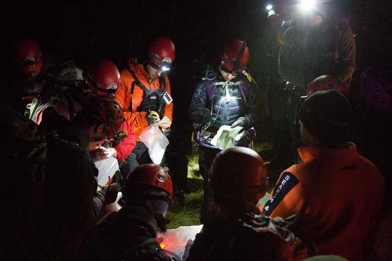 SUBMITTED PHOTO: GITTE VENDERBY - The MCSOSAR team huddles around to read maps, get their bearings and take stock during a mission that lasted well into the night. The Venderbys say theyre prepared to drop everyhting and head to a search mission at all times by keeping their packs ready to go.