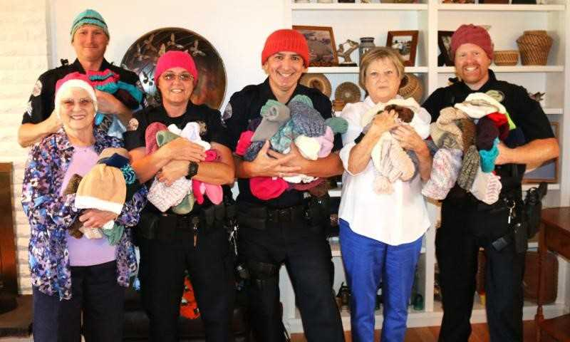 COURTESY PHOTO: CITY OF WOODBURN - The Metropolitan Machine Knitters Guild has tasked the Woodburn Police Department with distributing hats to children in community.