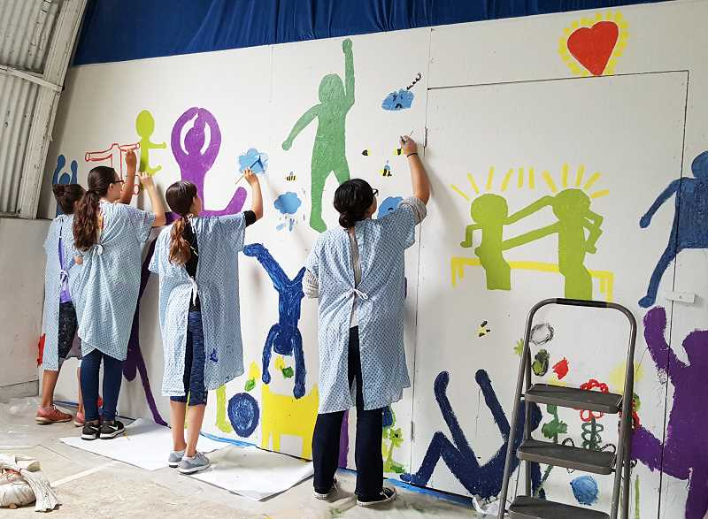SETH GORDON - Students paint a mural in the outdoor play area at St. Paul Parochial School. The project waspart of the Art Smarts program, which provides monthly arts curriculum through parent volunteers.