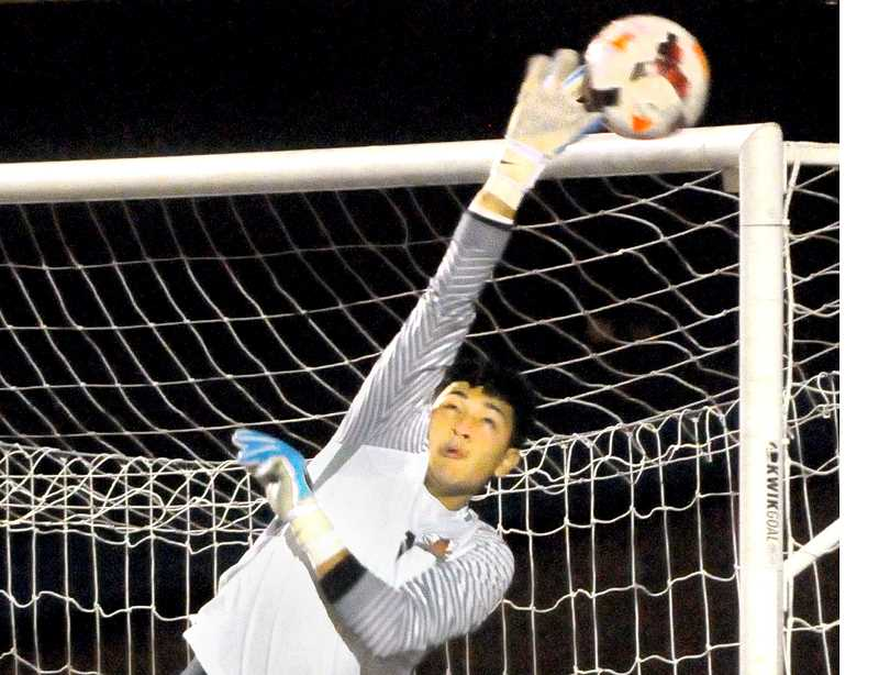 SETH GORDON - Newberg goalie Nick Elias stretches to get a finger on a free kick during Newberg's 2-0 home win over Tigard Oct. 3. The Tigers have won their first three Three Rivers League contests this season and risen to No. 6 in the state rankings.