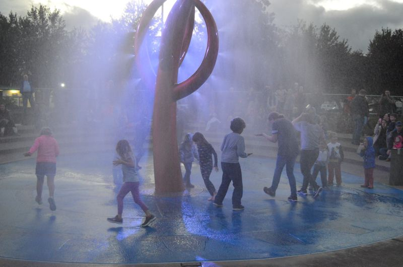 SPOTLIGHT PHOTO: COURTNEY VAUGHN - Children play under a newly installed 20-foot water fountain at Heritage Park in Scappoose. A public dedication ceremony was held Saturday, Oct. 7.