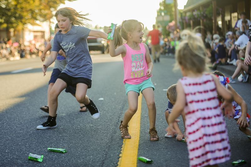 FILE PHOTO - Children scramble onto Pioneer Boulevard to pick up candy thrown during the 2017 Sandy Mountain Festival Parade. A new provision of the Oregon Department of Transportation street-closure permit will prohibit candy from being thrown during the parade. The provision does not prohibit handing out candy.