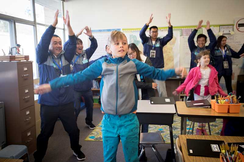 TIMES PHOTO: JAIME VALDEZ - Third-grader Devo Gantz, leads physical education teachers from China in an exercise activity at Raleigh Park Elementary School. Teachers from the Beaverton School District and from China visited the school during an Active Schools Innovation Awards event.
