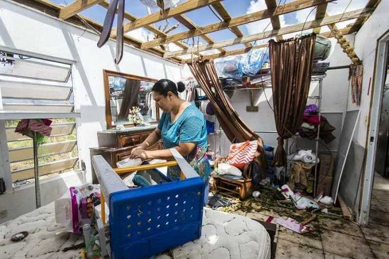 PHOTO COURTESY OF ULISES AVILES - A woman searches through what's left of her home in the wake of two hurricanes that devastated Puerto Rico earlier this month. More than 90 percent of the island is still without power.