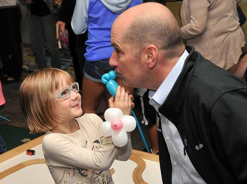 TIDINGS PHOTOS: VERN UYETAKE - Lucy and Keith Morris enjoy balloon animals.