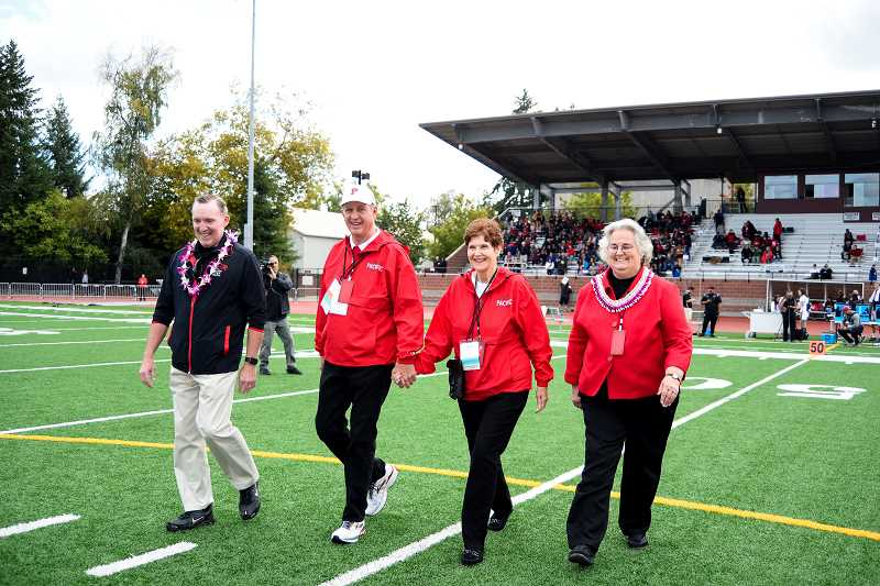 COURTESY PHOTO: TANNER BOYLE PHOTOGRAPHY - Pacific University Athletics Director Ken Schumann (left) and President Lesley Hallick (right) escort Kim and Barb Ledbetter to midfield for a pregame ceremony to honor the Ledbetters for their support toward the resurfacing of the playing field at Hanson Stadium