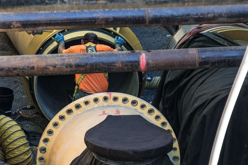TIMES PHOTO: JONATHAN HOUSE - A worker grasps a large steel pipe, part of the Willamette Water Supply transmission line under construction from Wilsonville to Hillsboro, at a development site near Aloha.
