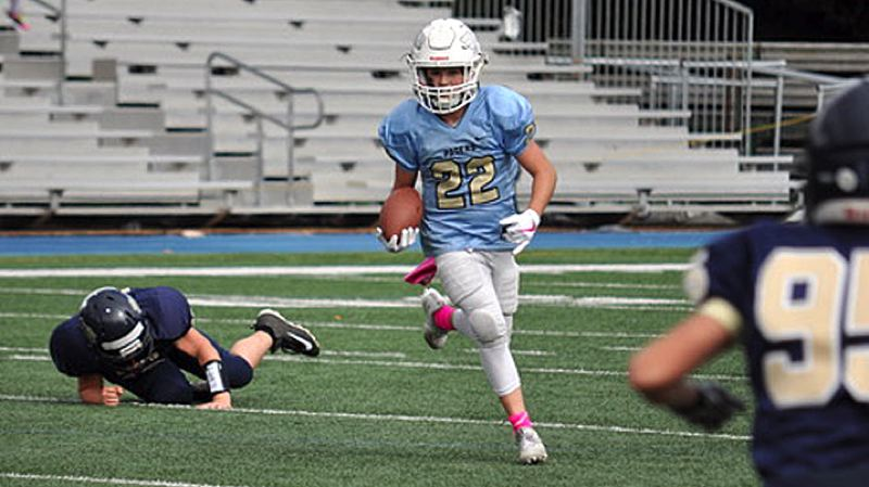 SUBMITTED PHOTO - A running back from the Pacers 5/6 White team speeds past a Canby defender during his team's 34-0 home win on Saturday.
