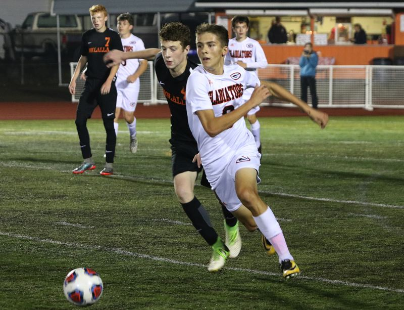 REVIEW/NEWS PHOTO: JIM BESEDA - Gladstone's Konnor Hathaway (right) has a half-step on Molalla's Logan Child as he drives the ball out of the Gladiators' end during Tuesday's Tri-Valley Conference boys' soccer match.