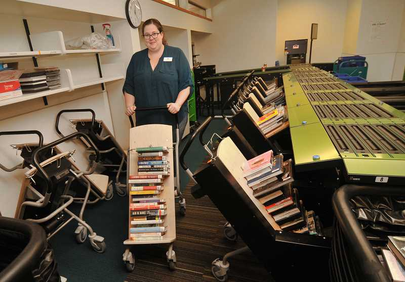 REVIEW PHOTO: VERN UYETAKE - Library volunteer Anya Woodhouse wheels out one of the sorting machine's detachable stacking carts, which can be raised up to a horizontal positon so library staff and volunteers don't have to bend over to lift them back on to the shelves.