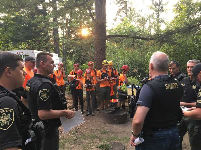 SUBMITTED PHOTO: GITTE VENDERBY - Members of the Multnomah County Sheriff's Office Search and Rescue team receive instructions from deputies during a mission earlier this year. The Venderbys say they're prepared to drop everything and head to a search mission at all times by keeping their packs ready to go.