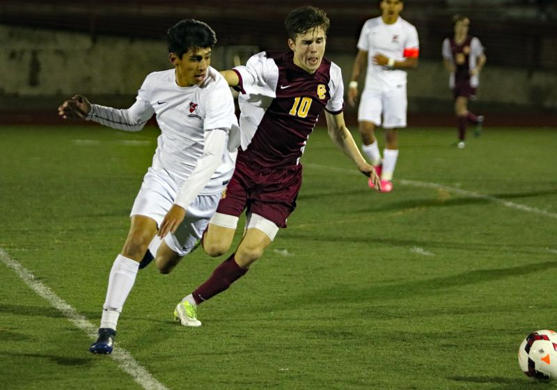 REVIEW/NEWS PHOTO: JIM BESEDA - Oregon City's Edson Jimenez-Sutton (left) and Central Catholic's Liam Anderson (10) chase after a loose ball in the second half of Wednesday's Mt. Hood Conference boys' soccer match.