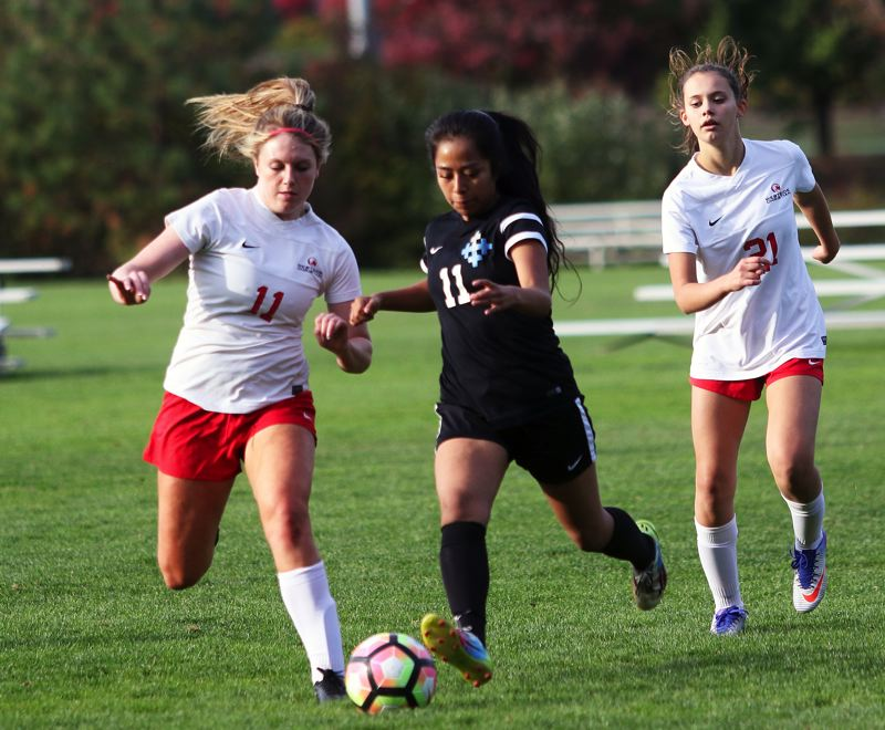 DAN BROOD - Westside Christian senior Gabrielle Lau (left) races for the ball during Monday's match.