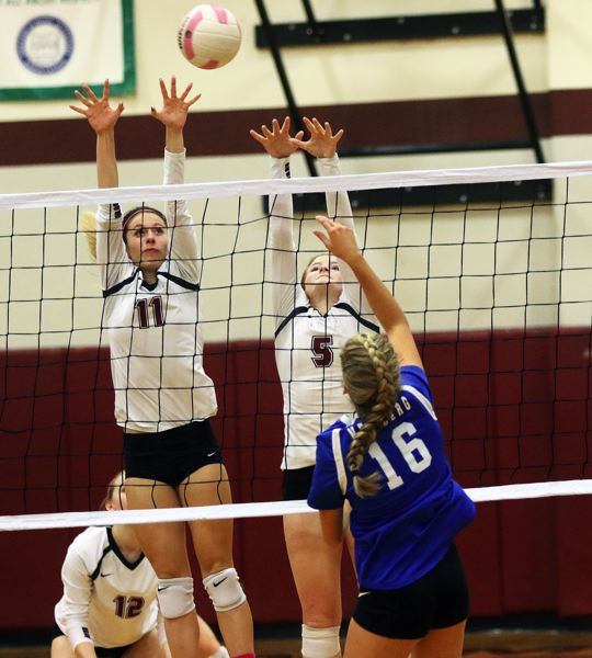 DAN BROOD - Sherwood sophomore Claire McGill (11) and senior Grace Rivers go up for a block during the win over Newberg.