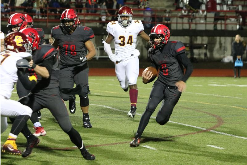 REVIEW/NEWS PHOTO: JIM BESEDA - Oregon City's Teron Bradford (with ball) finds running room on the left side, scoring on a 5-yard run in the third quarter of Thursday's home game against Central Catholic.