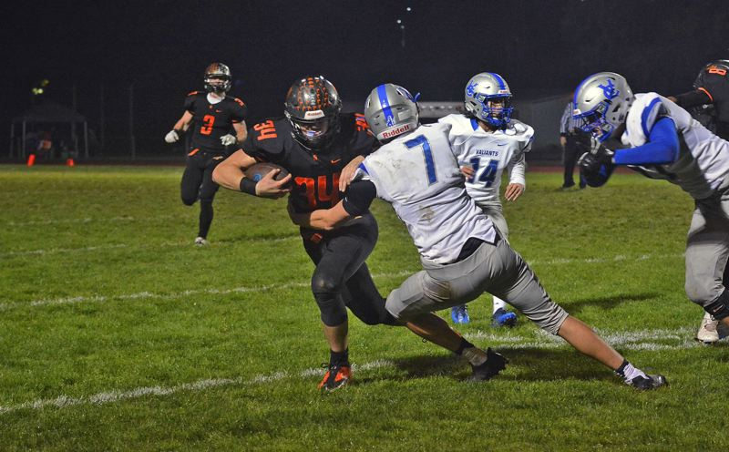 TIMES PHOTO: MATT SINGLEDECKER - Scappoose junior running back Matt Roth tries to shed a Valley Catholic tackle attempt.