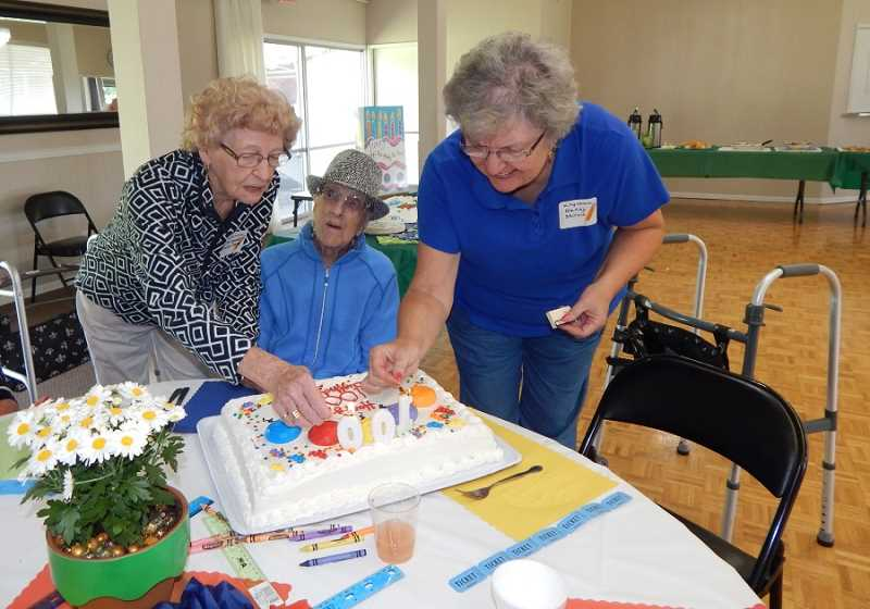 BARBARA SHERMAN - The King City Women's Golf Club's Sept. 20 luncheon coincided with the 100th birthday of longtime member Dorothy Gross (center), and Margaret Wells, left, and club social member Nancy Skirvin lit candles on one of two cakes for Gross to blow out.