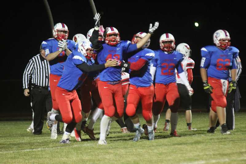 WILL DENNER/MADRAS PIONEER - Madras senior Brady Pattenaude (center) and teammates celebrate after Pattenaude scored a touchdown 17 seconds into the second half. The score and two-point conversion gave the Bufs a 22-8 lead.