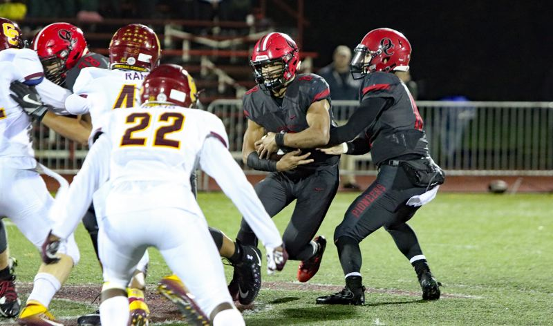 REVIEW/NEWS PHOTO: JIM BESEDA - Oregon City's Zakayas Dennis-Lee (with ball) was held for no gain on fourth-and-2 from Central Catholic's 49-yard line with 1:59 to play in Thursday's Mt. Hood Conference game.