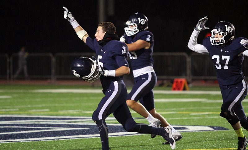 PAMPLIN MEDIA GROUP PHOTO: MILES VANCE - Lake Oswego's (from left) Matt Sebolsky, Marshall McGuire and Bryson Breeze race toward the Laker crowd at the end of their team's 21-20 home win over West Linn on Friday night.
