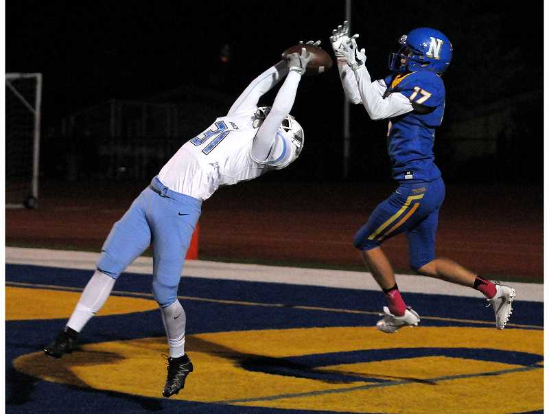 SETH GORDON - Lakeridge defensive back Jared Bartunek outduels Newberg wide receiver Davis Smith on a jump ball to record an interception during the Pacers' 36-0 road victory Friday night.