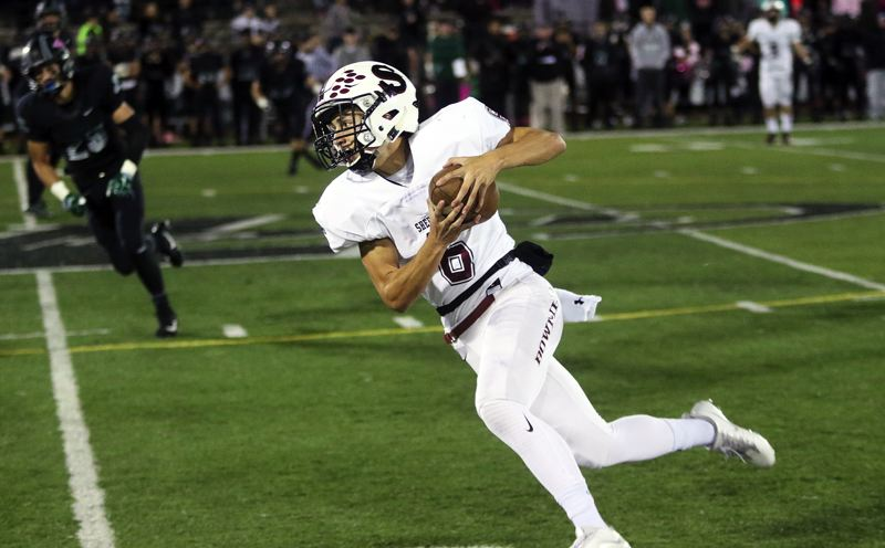 DAN BROOD - Sherwood junior Jacob Reuter takes off after catching a pass in Friday's game at Tigard.