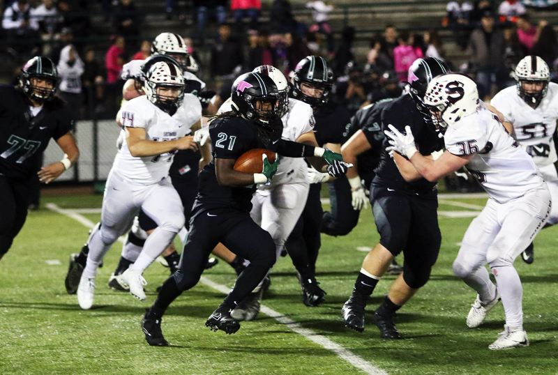 DAN BROOD - Tigard junior running back Malcolm Stockdale follows his blockers during Friday's game with Sherwood.