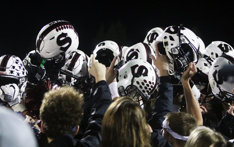 DAN BROOD - The Bowmen raise their helmets in celebration following the win at Tigard.