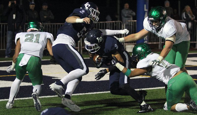 PAMPLIN MEDIA GROUP PHOTO: MILES VANCE - Lake Oswego's Jordan Newlin (center) powers into the end zone for a 10-yard touchdown that paved the way for his team's 21-20 home win over West Linn on Friday night.