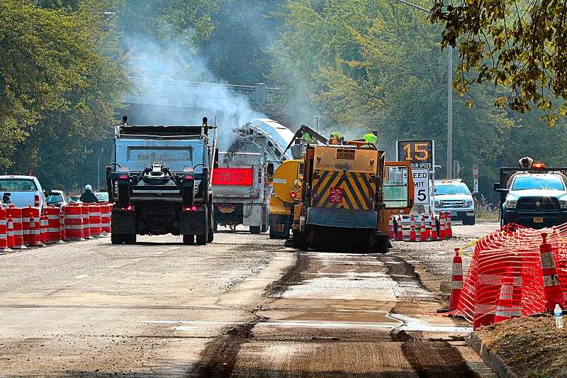 DAVID F. ASHTON - A massive road surface grinder here was mincing a layer of pavement and shooting it into a waiting truck; the remaining debris was then picked up by an industrial street sweeper.