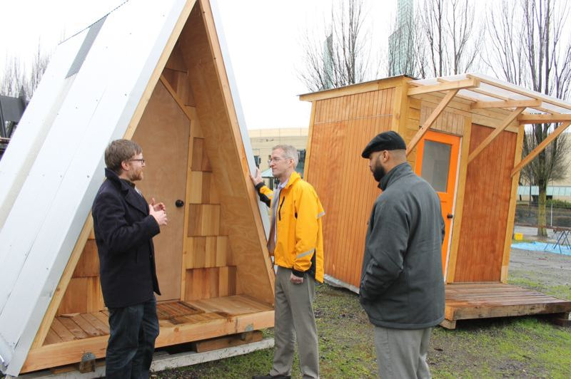 PORTLAND TRIBUNE: LYNDSEY HEWITT - Todd Ferry of PSU's Center for Public Interest Design talks to make Ted Wheeler outside a number of tiny homes in March. The were moved to the city-sanctioned village for homeless women in Kenton.