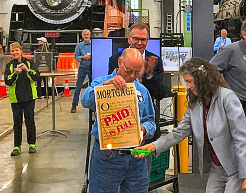 COURTESY CITY OF PORTLAND - City Commissioner Amanda Fritz came to the Rail Heritage Museum near OMSI to burn the now-paid-off mortgage provided by the city, as Commissioner Nick Fish applauds in the background.