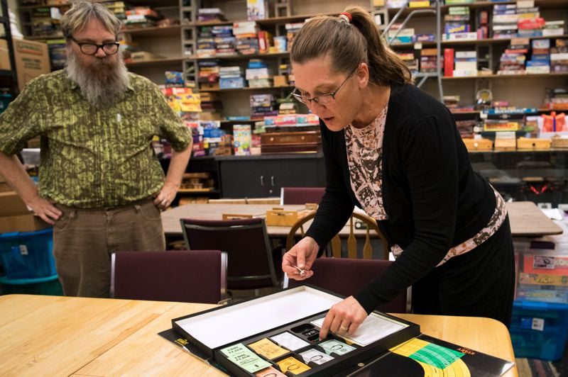 TIMES PHOTO: JAIME VALDEZ - Kyle Engen watches as his wife, Carol Mathewson, opens a Win, Place & Show 3M board game at the new location of the Interactive Museum of Gaming and Puzzlery (IMOGAP) in King City.